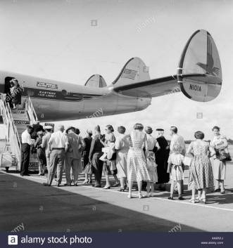 1950s-tail-of-commercial-aviation-airplane-on-tarmac-with-passengers-AAKN1J